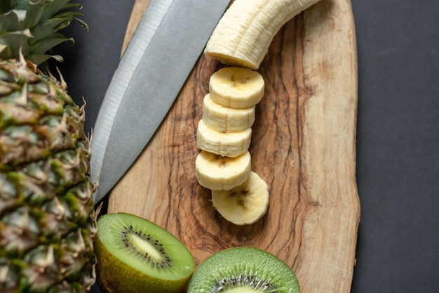 Bovenaanzicht van een ananas op tafel met gehakte bananen en kiwi's op een houten snijplank