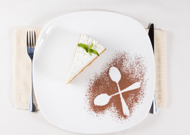 Bovenaanzicht van een artistieke plating van een plakje taart gegarneerd met room geserveerd als dessert met de contouren van twee gekruiste lepels in cacaopoeder als decoratie