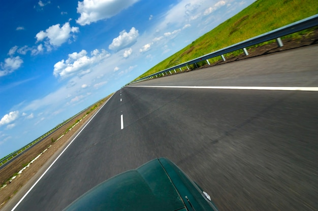 Bovenaanzicht van een auto is een gladde snelweg omgeven door mooie zomerse natuur met velden met groene bomen en blauwe lucht op een zonnige warme zomerdag