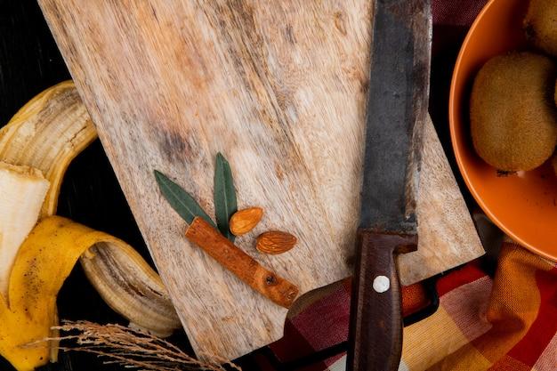 Bovenaanzicht van een banaan-fruit met amandel, kaneelstokjes en oude keukenmes op een houten snijplank op zwart