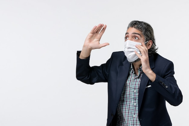 Bovenaanzicht van een bange jonge kerel in een pak die een masker draagt en omhoog kijkt op een witte achtergrond