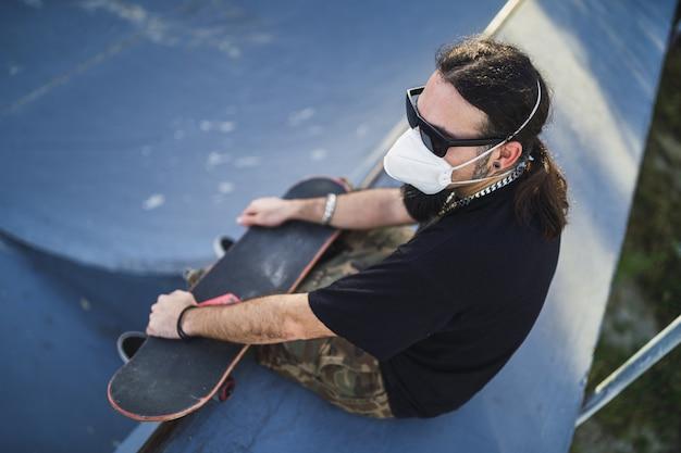 Bovenaanzicht van een bebaarde man die een gezichtsmasker draagt, zittend op een betonnen ondergrond