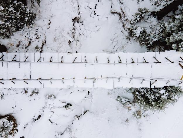 Bovenaanzicht van een besneeuwde brug in de kopieerruimte van het bos