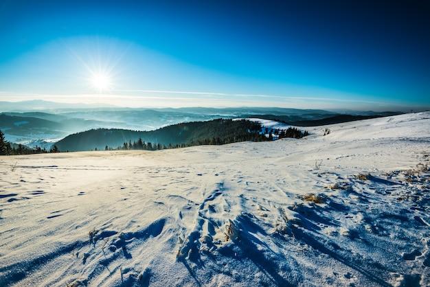 Bovenaanzicht van een besneeuwde skipiste op de achtergrond van heuvels bedekt met bomen