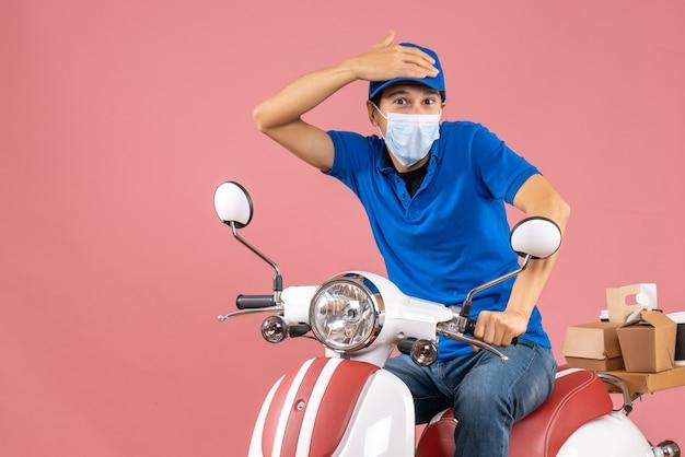 Bovenaanzicht van een bezorgde bezorger met een medisch masker met een hoed op een scooter op een pastelkleurige perzikachtergrond