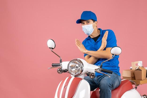 Bovenaanzicht van een bezorger met een medisch masker met een hoed die op een scooter zit en een stopgebaar maakt op een pastelkleurige perzikachtergrond