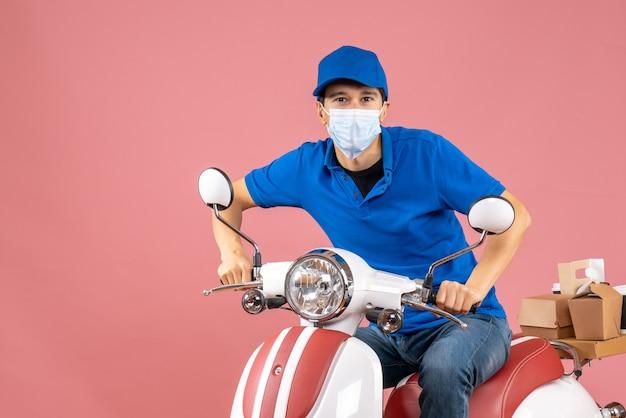 Bovenaanzicht van een bezorger met een medisch masker met een hoed die op een scooter zit en voor de camera poseert op een pastelkleurige perzikachtergrond