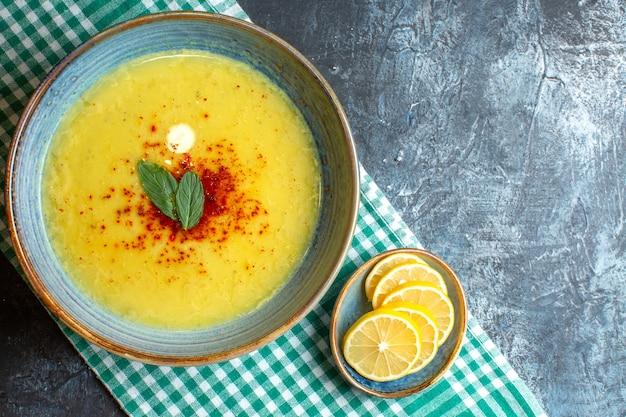Bovenaanzicht van een blauwe pot met smakelijke soep geserveerd met munt en gehakte citroen op halfgevouwen groene gestripte handdoek op blauwe achtergrond