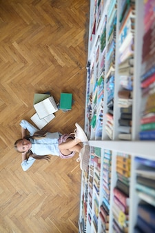 Bovenaanzicht van een blij dromerig schoolkind dat op de vloer ligt in een openbare bibliotheek en omhoog kijkt