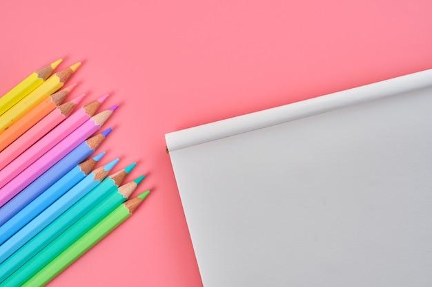 Bovenaanzicht van een blocnote en kleurpotloden op een roze achtergrond met kopie ruimte