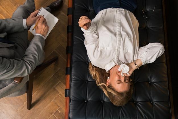 Bovenaanzicht van een blonde depressieve vrouw die tranen vergiet in de aanwezigheid van haar arts tijdens de therapiesessie