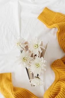 Bovenaanzicht van een boek met witte chrysantenbloemen op een witte achtergrondstof en een gele trui