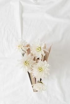 Bovenaanzicht van een boek met witte chrysantenbloemen op witte achtergrondstof