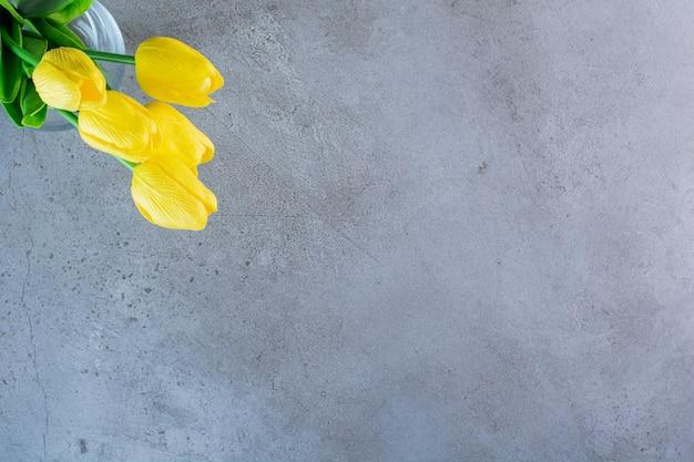 Bovenaanzicht van een boeket gele tulpen in een glazen vaas op de grijze achtergrond.