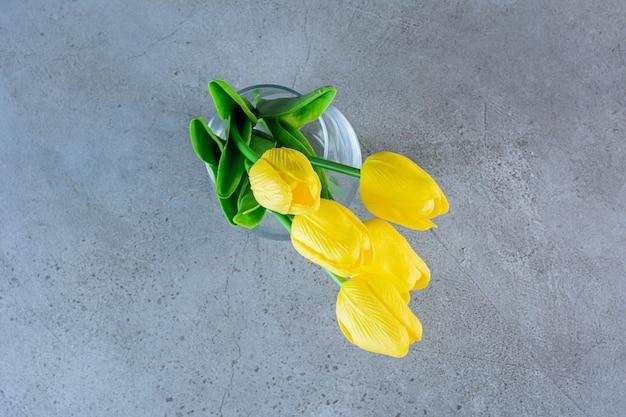 Bovenaanzicht van een boeket gele tulpen in een glazen vaas op het grijs