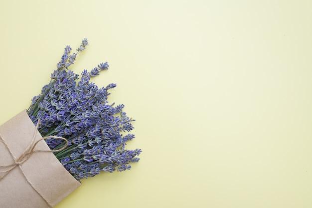 Bovenaanzicht van een boeket lavendel in een knutseltas op een gele ondergrond