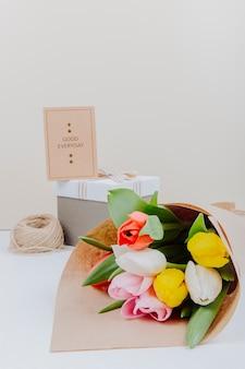 Bovenaanzicht van een boeket van kleurrijke tulp bloemen in een ambachtelijke papier op witte achtergrond