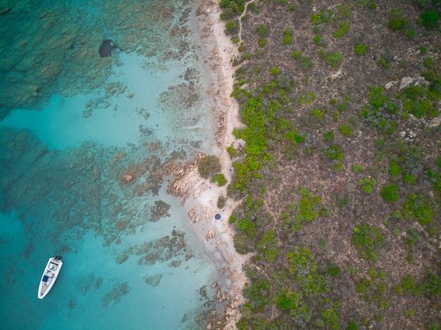 Bovenaanzicht van een boot op de blauwe zee bij de kust