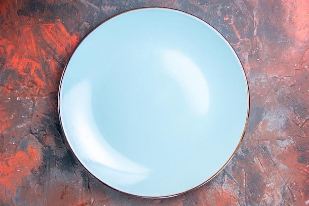 Bovenaanzicht van een bord blauw rond bord in het midden van de tafel