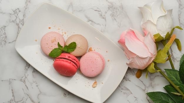 Bovenaanzicht van een bord franse kleurrijke macarons op marmeren bureau versierd met rozenbloem
