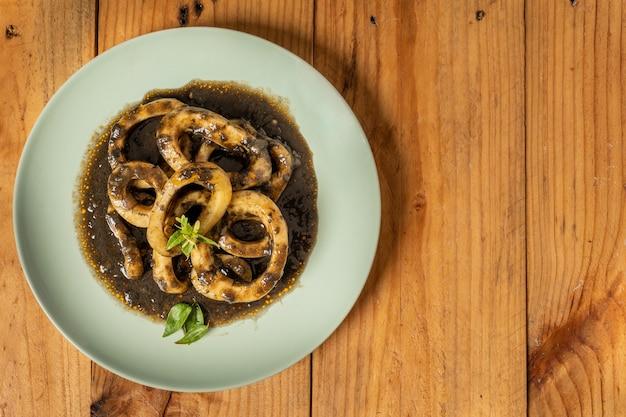 Bovenaanzicht van een bord heerlijke calamares bereid met inkt en sauzen
