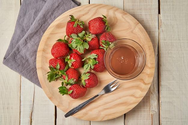 Bovenaanzicht van een bord met aardbeien en chocolade