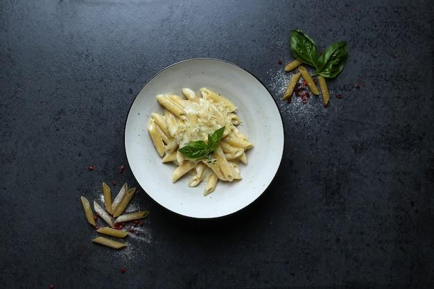 Bovenaanzicht van een bord pasta met kaassaus en basilicum op de zwarte tafel