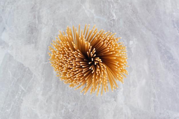 Bovenaanzicht van een bos spaghetti op het marmer