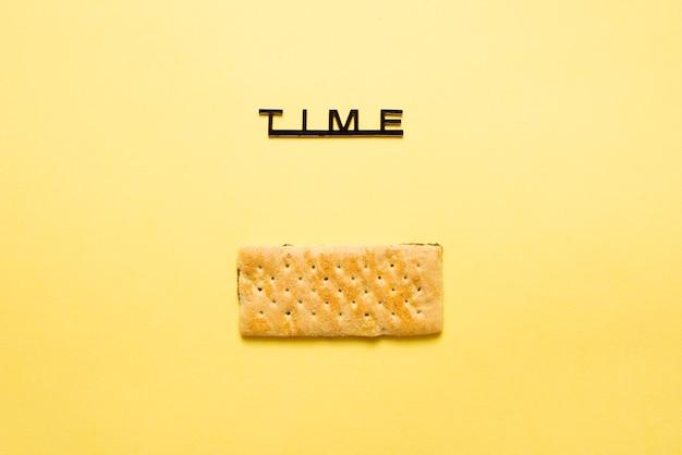 Bovenaanzicht van een boterachtige cracker met gaten en zout op gele achtergrond