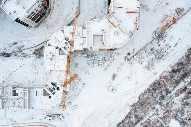 Bovenaanzicht van een bouwplaats met kranen bedekt met sneeuw. luchtfoto stadsgezicht.