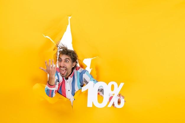 Bovenaanzicht van een boze en emotionele jongeman die tien procent laat zien in een gescheurd gat in geel papier