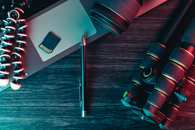 Bovenaanzicht van een bureau werkt met laptop toetsenbord, moderne camera, statief en een pen