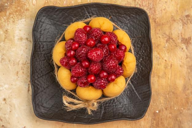 Bovenaanzicht van een cadeau-cake met fruit op gemengde kleur achtergrond