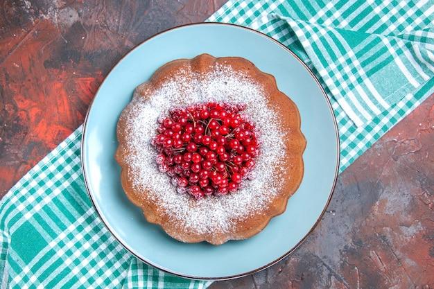 Bovenaanzicht van een cake een smakelijke cake met rode aalbessen op het geruite tafelkleed