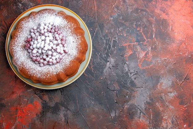 Bovenaanzicht van een cake met bessen een smakelijke cake met rode aalbessen en suiker Gratis Foto