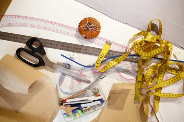 Bovenaanzicht van een centimeter geel, schaar, liniaal en andere hulpmiddelen van de naaister