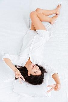 Bovenaanzicht van een charmante jonge vrouw die in bed ligt en een overwinningsgebaar toont