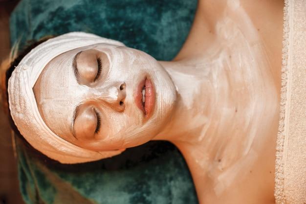 Bovenaanzicht van een charmante jonge vrouw die met gesloten ogen met een masker op haar gezicht en lichaam in een kuuroord rust.
