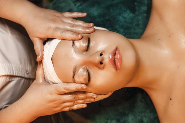 Bovenaanzicht van een charmante vrouw die rust terwijl het hebben van huidverzorgingsroutine in een wellness-kuuroord.