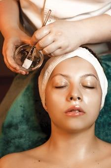 Bovenaanzicht van een charmante vrouw leunend met gesloten ogen met een masker met hyaluronzuur in een wellness-kuuroord.