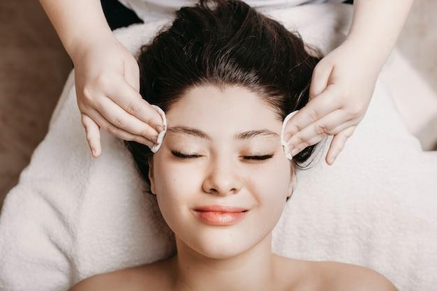 Bovenaanzicht van een charmante vrouw met donker haar, leunend op een spa-bed met gesloten ogen terwijl ze huidroutine heeft voor gezichtsbehandeling in een spa-centrum.