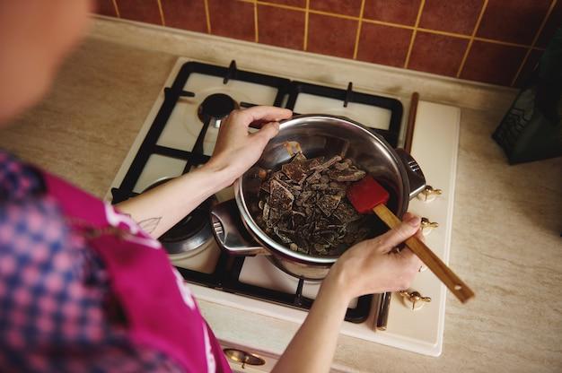Bovenaanzicht van een chocolatier banketbakker smeltende chocolade in een waterbad
