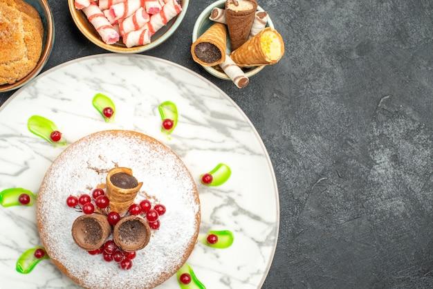 Bovenaanzicht van een close-up een cake een smakelijke cake met bessen, snoepjes, koekjes, wafels