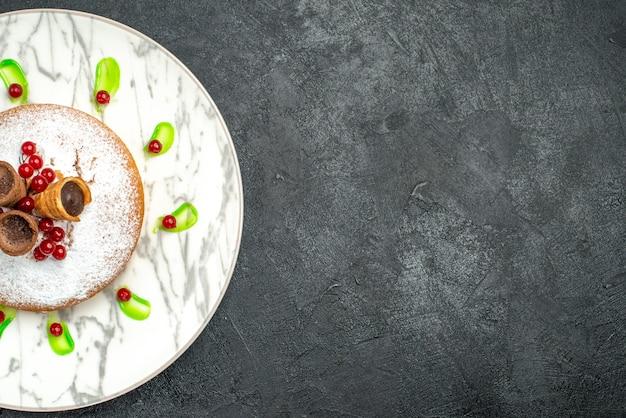 Bovenaanzicht van een close-up een cake grijze plaat van een cake met bessen groene saus wafels