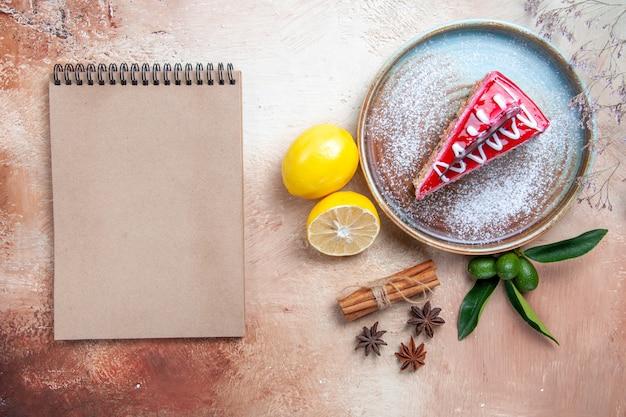 Bovenaanzicht van een close-up een cake plaat van cake citrusvruchten kaneelstokjes steranijs crème notebook