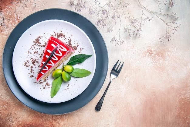Bovenaanzicht van een close-up een cake plaat van cake met chocoladesausen citrusvruchten vork