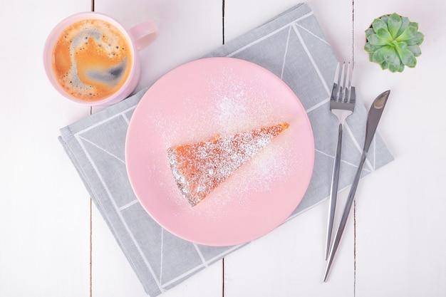 Bovenaanzicht van een close-up van een stuk taart op een roze bord met een mes en een vork op een gevouwen linnen servet met een geometrisch patroon en een mok met koffie. zelfgemaakt bakken. selectieve aandacht.