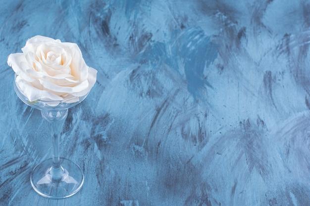 Bovenaanzicht van een cocktailglas met witte roze bloem.