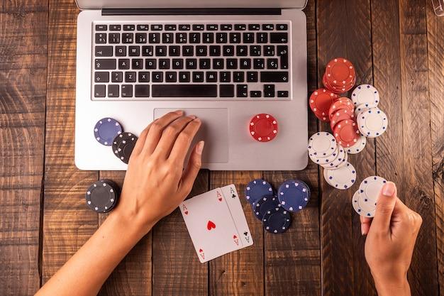 Bovenaanzicht van een computer met pokerfiches en kaarten om in te zetten of te spelen.