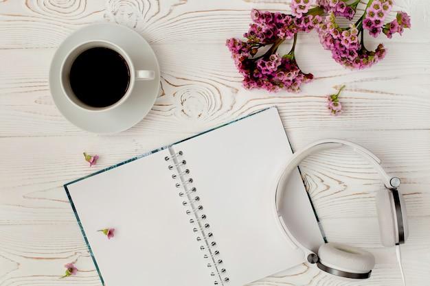 Bovenaanzicht van een dagboek of laptop, koptelefoon en koffie en een paarse bloem op een witte houten tafel. romantisch plat ontwerp.